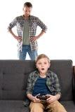 Poważny ojciec patrzeje syna obsiadanie na kanapie z joystickiem z rękami na talii Obraz Stock