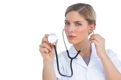 Poważny pielęgniarki słuchanie z stetoskopem Zdjęcia Stock