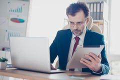 Poważny pracownik pisać na maszynie informację od pastylki laptop On i zdjęcia royalty free