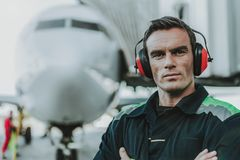 Poważny przystojny pracownik ma pracę w aerodromu obraz royalty free