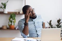 Poważny rozważny afrykański biznesmena obsiadanie przy biurkiem obraz stock