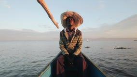 Poważny rybak w słomianym kapeluszu siedzi w łodzi Mężczyzna iść morze w Afryka przy świtem w ranku zbiory