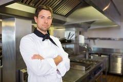 Poważny samiec kucharz z rękami krzyżował w kuchni fotografia stock