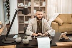 Poważny skoncentrowany mężczyzna pisać na maszynie na maszynie do pisania w popielatym kardiganie fotografia royalty free