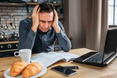 Poważny skoncentrowany mężczyzna siedzi przy stołem w kuchni Trzyma ręki dalej czyta czasopismo i Mężczyzna praca zdjęcia royalty free