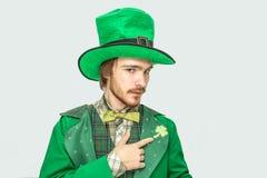 Poważny skoncentrowany młody readhead mężczyzny punkt na koniczynie na kostiumu Jest ubranym zielonych ubrania i kapelusz Faceta  zdjęcia stock
