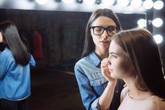 Poważny skoncentrowany makeup artysta patrzeje jej klienta zdjęcie stock