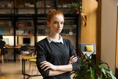 Poważny skoncentrowany rudzielec damy uczeń pozuje indoors w bibliotece zdjęcia stock