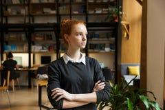 Poważny skoncentrowany rudzielec damy uczeń pozuje indoors w bibliotece fotografia royalty free