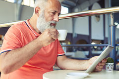 Poważny starszy brodaty mężczyzna pije kawę Fotografia Royalty Free