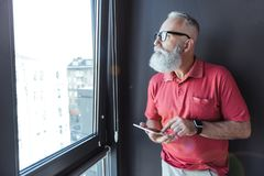 Poważny stary z włosami biznesmen trzyma nowożytnego gadżet Fotografia Stock