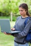 Poważny studencki pisać na maszynie na jej laptopie Zdjęcia Royalty Free