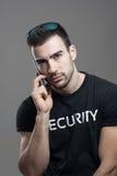 Poważny twardy agent ochrony opowiada na telefonie patrzeje kamerę Obrazy Royalty Free
