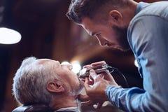 Poważny ufny fryzjer męski żyłuje jego klient brodę Zdjęcie Royalty Free