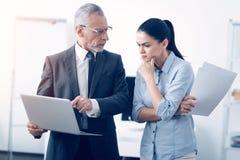 Poważny urzędnik i szef dyskutuje biznesowego dokument na laptopie obraz stock