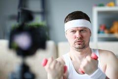 Poważny Vlogger Robi ćwiczeniu z Dumbbells zdjęcie royalty free