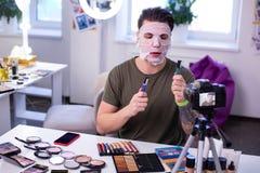Poważny z włosami mężczyzna porównuje różnego makeup produkt w zielonej koszulce zdjęcia stock