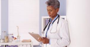 Poważna Czarna senior lekarka pracuje na pastylce w biurze Zdjęcia Stock