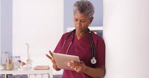 Poważna Czarna senior lekarka pracuje na pastylce w biurze Obrazy Stock