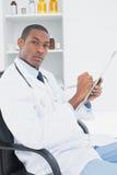 Poważna lekarka pisze recepcie w medycznym biurze Zdjęcia Stock