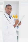 Poważna lekarka pisze recepcie w medycznym biurze Zdjęcie Royalty Free