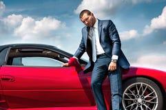 Poważny biznesmen stoi blisko samochodu Zdjęcia Royalty Free