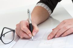 Poważny biznesowej kobiety writing na jej agendzie w biurze Obrazy Royalty Free
