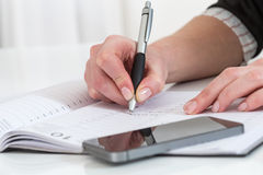 Poważny biznesowej kobiety writing na jej agendzie w biurze Zdjęcia Stock