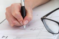 Poważny biznesowej kobiety writing na jej agendzie w biurze Obrazy Stock