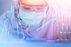 Poważny klinicysta patrzeje ciecz w kolbie podczas badania medyczne Obraz Stock