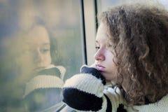 Poważny nastoletniej dziewczyny obsiadanie okno obraz stock