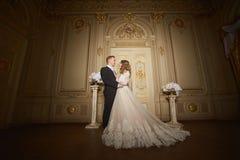 Powabna ślub para w wnętrzu w baroku stylu ściska each inny na wielkim pałac królewskim Fotografia Stock