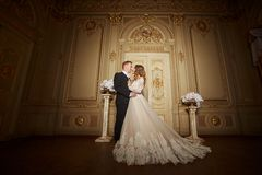 Powabna ślub para w wnętrzu w baroku stylu ściska each inny na wielkim pałac królewskim Obraz Stock