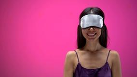 Powabna ?e?ska jest ubranym oko maska dla spa? i ono u?miecha si? na r??owym tle fotografia stock