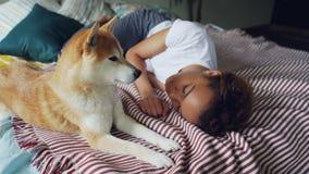 Powabna amerykanin afrykańskiego pochodzenia dama śpi na drewnianym łóżku z nowożytną pościelą podczas gdy jej śliczny lojalny pi zbiory
