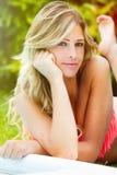 Powabna blondynki dziewczyna w swimsuit bikini łgarskim puszku na jej żołądku Obrazy Stock