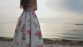 Powabna brunetka w długiej wieczór sukni stoi bezczynnie rzekę zbiory