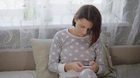 Powabna brunetki kobieta z krótkim ostrzyżeniem ubierającym w popielatych pyjamas siedzi na kanapie w sypialni i używa ona zdjęcie wideo