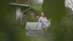 Powabna caucasian młoda kobieta zabawa tana i śpiew przy podwórko podczas gdy robić domowej pracie z pościelą zdjęcie wideo