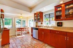 Powabna czereśniowa drewniana kuchnia z dachówkową podłoga. Zdjęcie Stock