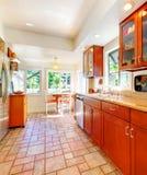 Powabna czereśniowa drewniana kuchnia z dachówkową podłoga. Obrazy Stock
