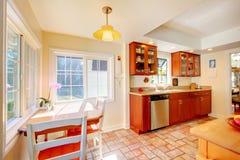 Powabna czereśniowa drewniana kuchnia z dachówkową podłoga. Zdjęcie Royalty Free