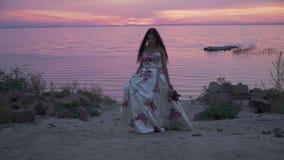 Powabna dama w długiej sukni na pięknej plaży zdjęcie wideo