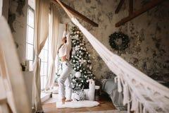 Powabna dziewczyna ubiera? w bia?ych puloweru, spod? stojakach obok nowego roku drzewa przed i rozci?gliwo?? i okno obraz royalty free