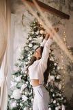 Powabna dziewczyna ubiera? w bia?ych puloweru, spod? stojakach obok nowego roku drzewa przed i rozci?gliwo?? i okno zdjęcia royalty free