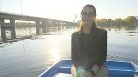Powabna dziewczyna w łodzi na tle słońce promienie Piękny uśmiech na jego twarzy Piękny miejsce swobodny ruch zdjęcie wideo