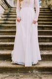 Powabna dziewczyna w długiego bielu smokingowy iść w dół antyka kamienia schodkami Fotografia Stock