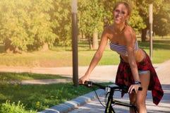 Powabna dziewczyna w parku na rowerze obraz royalty free