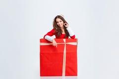 Powabna dziewczyna w Santa Claus kostiumowym obsiadaniu wśrodku prezenta pudełka Zdjęcie Royalty Free