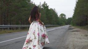 Powabna dziewczyna w wieczór sukni chodzi na drodze outdoors zbiory wideo